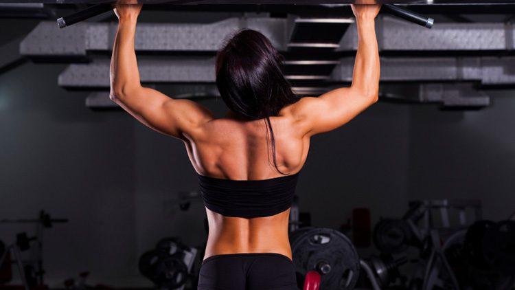 Los mejores ejercicios para ganar músculo en fitness. Practicando press frontal con barra/military press.